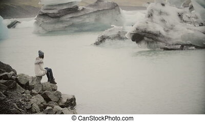 Young attractive woman sitting on the rock in ice lagoon....