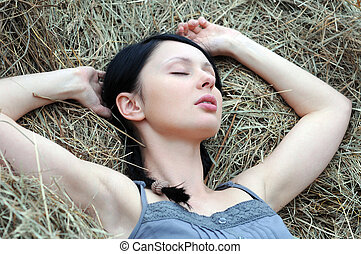 young attractive woman sleep on the haystack