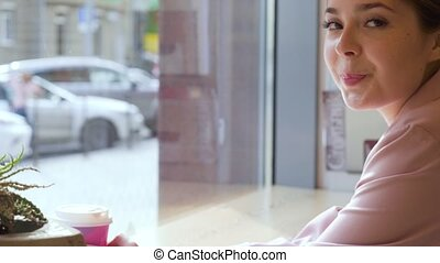Young attractive woman smiling to camera in cafe.