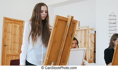 Young attractive woman standing behind the easel close up -...