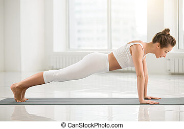 Young attractive woman standing in Plank pose, white color...