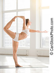 Young attractive woman standing in Natarajasana pose, white colo