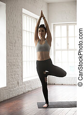 Young attractive woman standing in Vrksasana pose, white loft st