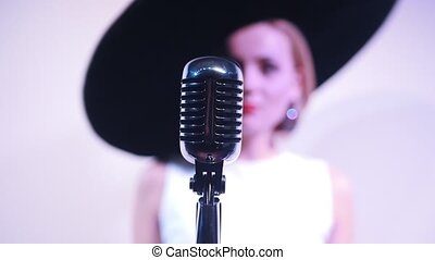 Young attractive woman standing near the mic on the background of a white wall in big hat. Mic in focus