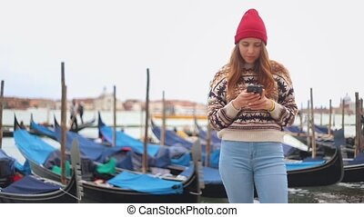 Young attractive woman staying on the waterfront and looks...