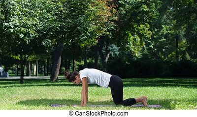 Young attractive woman stretching, exercising in the park. Yoga