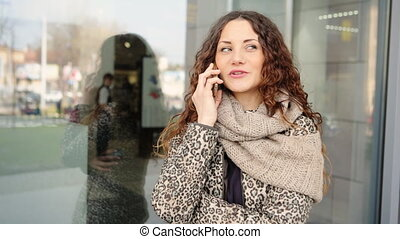 Young attractive woman talking on the mobile phone in the street.