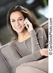 young attractive woman talking on the telephone at home