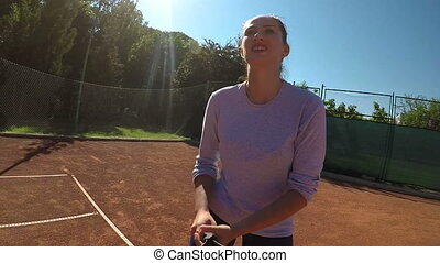 Young attractive woman tennis player serves on field and is...
