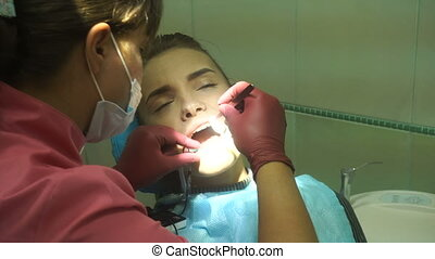 young attractive woman treats her teeth from a dentist