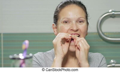 Young attractive woman using dental floss in the bathroom of the hotel room. She carefully chitit holes between the teeth and check the result at the end