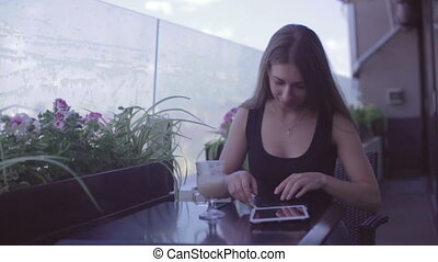 Young attractive woman using laptop while sitting in cafe