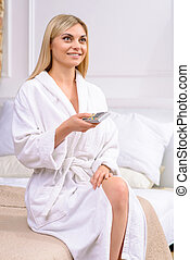 Young attractive woman using remote control.