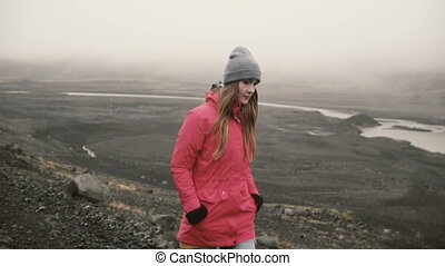 Young attractive woman walking in volcanic black mountains...
