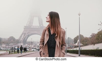 Young attractive woman walking near Eiffel tower in Paris,...