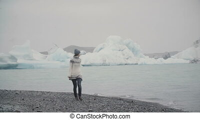 Young attractive woman walking on the shore of ice lagoon. Tourist exploring the famous sight with glaciers in Iceland.