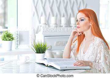 Young attractive woman with book in the morning