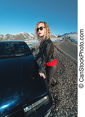 Young attractive woman with curly hair in sunglasses next to an old school car on a country road in the mountains