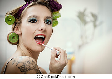 young attractive woman with hair roller is painting her lips