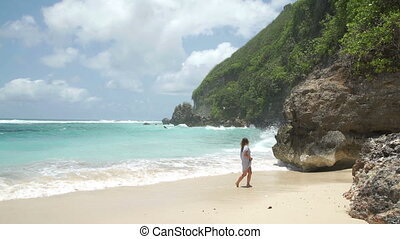 Young attractive woman with long hair jogging on beach....