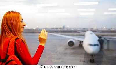 Young attractive woman with red hair and glasses looking at airplanes on runway airport