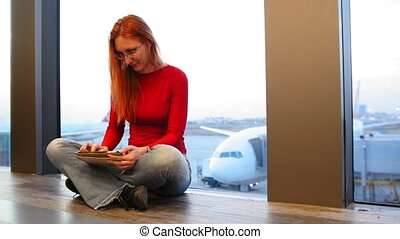Young attractive woman with red hair and glasses use gadget near window in the airport in front of airplanes