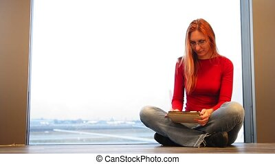Young attractive woman with red hair and glasses use gadget...