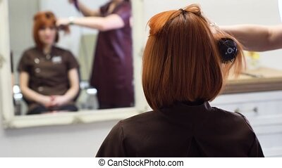 young attractive woman with red hair having Hair Cut at...