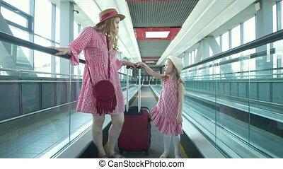 Young attractive woman with suitcase going down the escalator and her pretty daughter runs after her mother at the airport