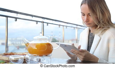 Young attractive woman with tablet computer sitting in cafe