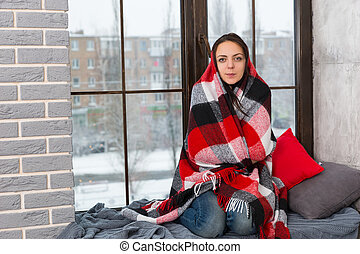 Young attractive woman wrapped in a blanket while sitting on the windowsill and looking at the camera