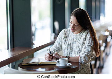 Young attractive woman writing diary in cafe