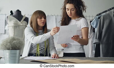 Young attractive women are looking at garment drawing and...