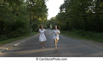 Young attractive women dressed in white running bare foot on...
