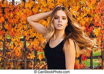 Young autumn woman with yellow leaves background. Outdoor fashion photo of girl beautiful hair surrounded .