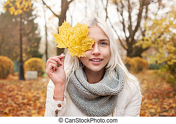 Young Autumn Woman with Yellow Maple Autumn Leaves on Fall Nature Background