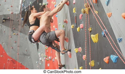 Young awesome couple doing aerobic exercise at climbing gym....