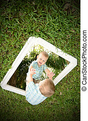 Young baby boy looking at self in mirror