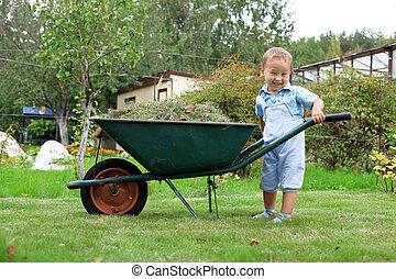 young baby boy pushing a wheelbarrow in garden