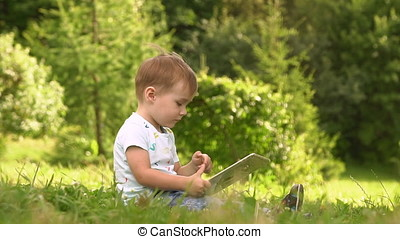 Young Baby Boy Using Smartphone Tablet Outside At Park.