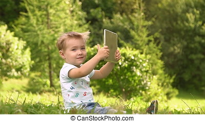 Young Baby Boy Using Tablet Computer Outside At Park.