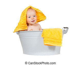Young baby having fun at bathtime sitting in a zinc tub with...