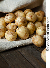 young (baby) potatoes in a sack on the wooden table