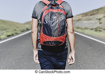 young backpacker man walking by a secondary road - closeup...