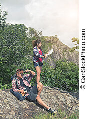 Young backpackers enjoying a valley view from top of a mountain in chiangmai thailand with vintage tone.