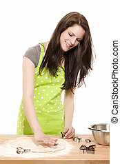 young baking woman using christmas molds on dough with white background