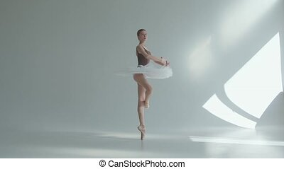 Young ballerina in pointe shoes and white ballet tutu makes ...