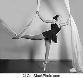 young ballerina in satin ballet shoes posing with a satin ribbons. black and white