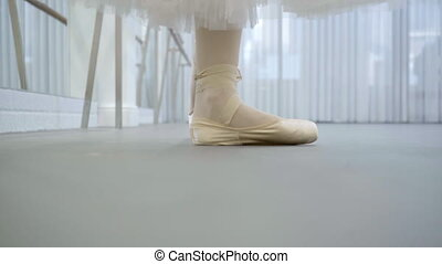 Young ballerina is practicing choreography in ballet school indoors.