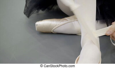 Young ballerina is tying tape of pointe shoes in modern...